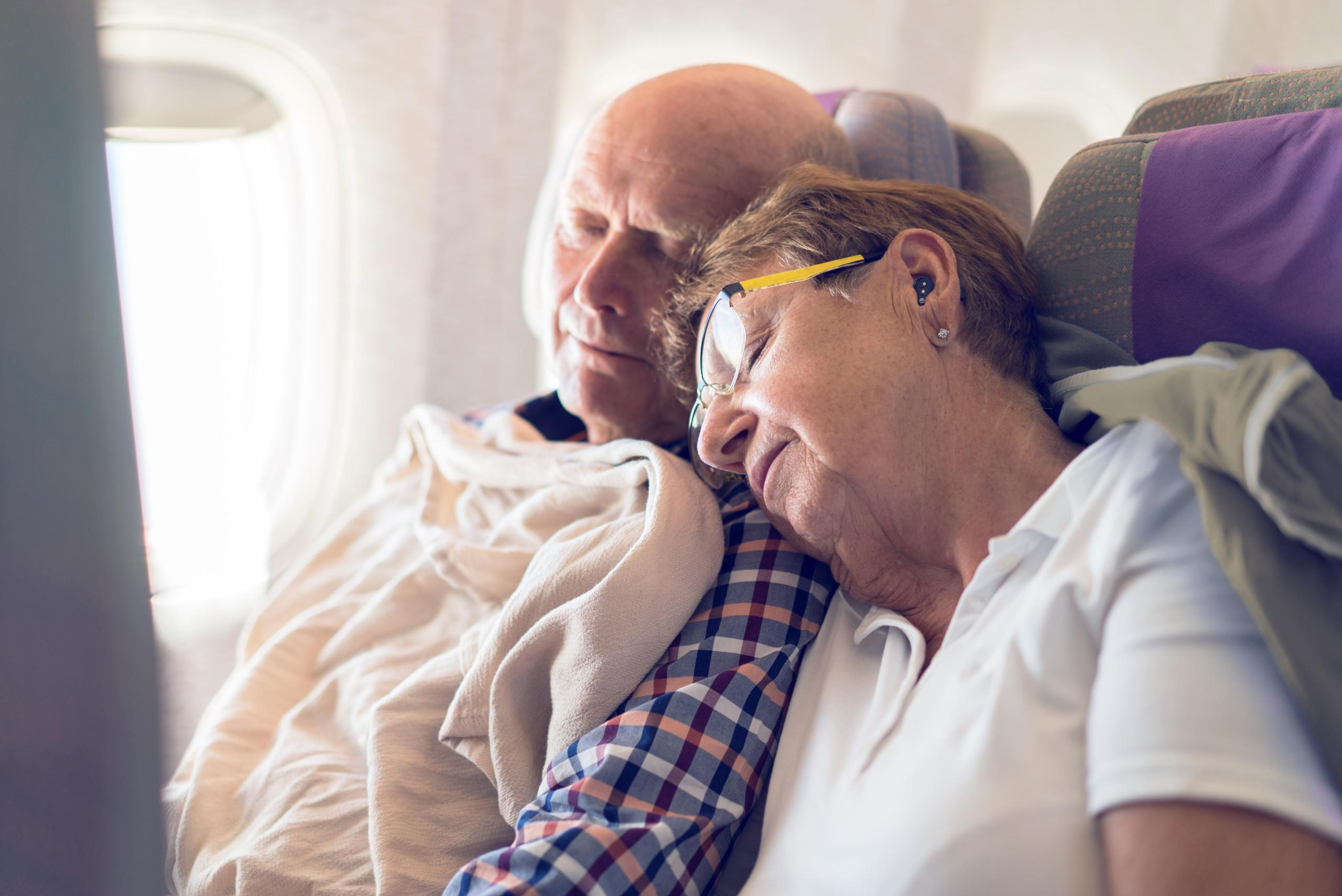 inflight - senior couple tourists in their seventies sleeping in airplane seat together with earbuds
